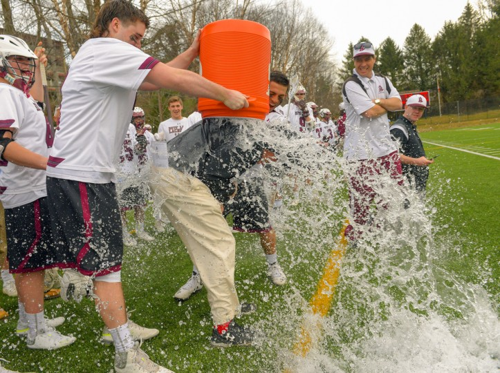 Boys' Latin seniors Devin Shewell, left, and teammate Anthony Wyler douse their   coach, Bob Shriver with ice water after he picks up his 500th career win with a 14-6 trouncing of South River Thursday afternoon in Baltimore.   on 4/2/15. (Doug Kapustin for BSMG)