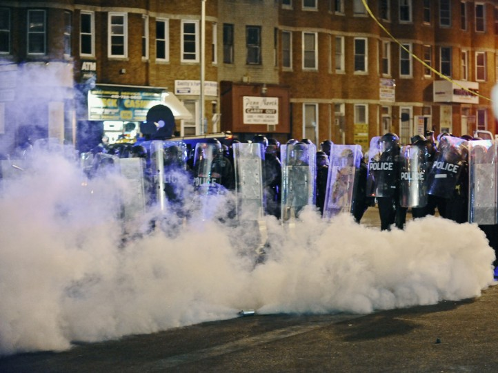 Baltimore City police use smoke canisters as they advance to clear protesters gathered at North and Pennsylvania avenues to enforce a 10pm to 5am curfew on Tuesday night. (Kenneth K. Lam/Baltimore Sun)