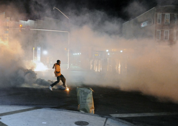 A protester kicks a smoke canister toward the police line at North and Pennsylvania avenues on Tuesday night, one day after a riot and wide spread looting resulting from the Freddie Gray protest. Baltimore City police use smoke and tear gas canisters to clear protesters to enforce a 10 pm to 5 am curfew.  (Kenneth K. Lam/Baltimore Sun)
