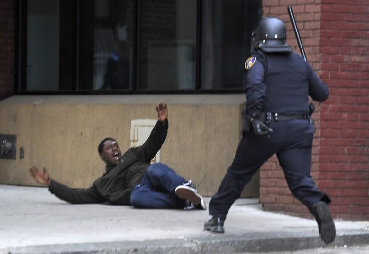 A Baltimore police officer approaches a man near Lexington Market before arresting him.  (Christopher T. Assaf/Baltimore Sun)