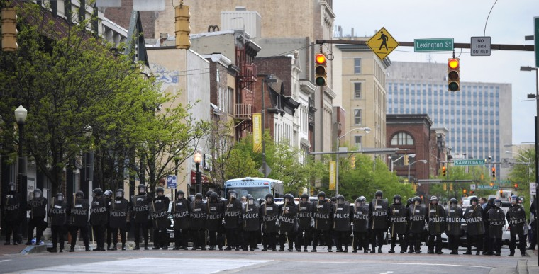 Police officers in riot gear block Howard Street near Lexington Market to prevent looting.  (Christopher T. Assaf/Baltimore Sun)