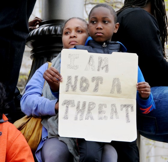 "Maurina Richardson-Frierson, Edgewater, and her son, Amir Frierson, 9, watch the rally at City Hall from an elevated position. Amir holds a sign that reads ""I Am Not A Threat"" that was created by his father.  March from Mount Street and Presbury Streets in Sandtown/WInchester where Freddie Gray was arrested to CIty Hall to and rally related to protest the death of  Gray in police custody.  (Kim Hairston/Baltimore Sun)"