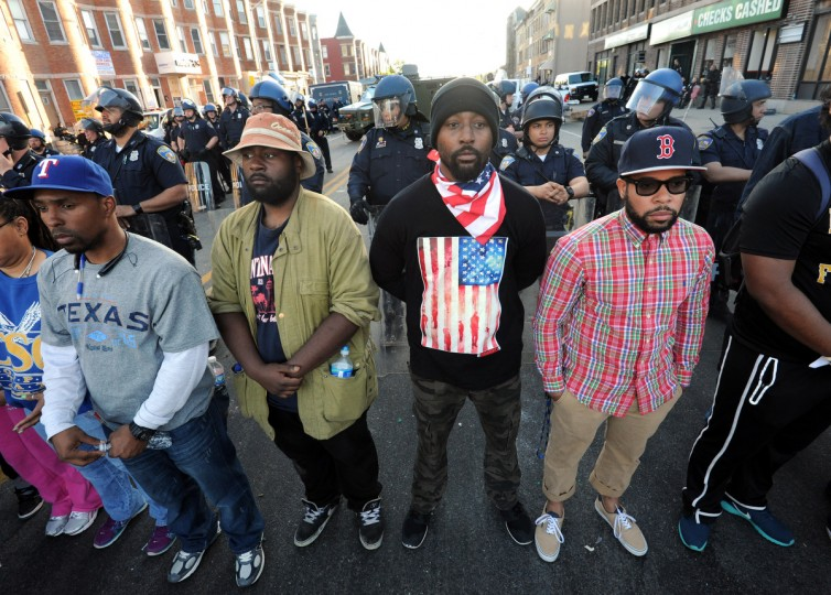 From left: Neil Jennings, 34, from Cherry Hill; Noah Smith, 25, from Pennsylvania  Ave.; Terry Mitchell, 32, from Park Heights, 32; and Ryan Johnson, 28, formerly from Baltimore. The mood is festive at North Ave. and Pennsylvania Ave., twenty-four hours after rioting in the same intersection.  (Algerina Perna/Baltimore Sun)