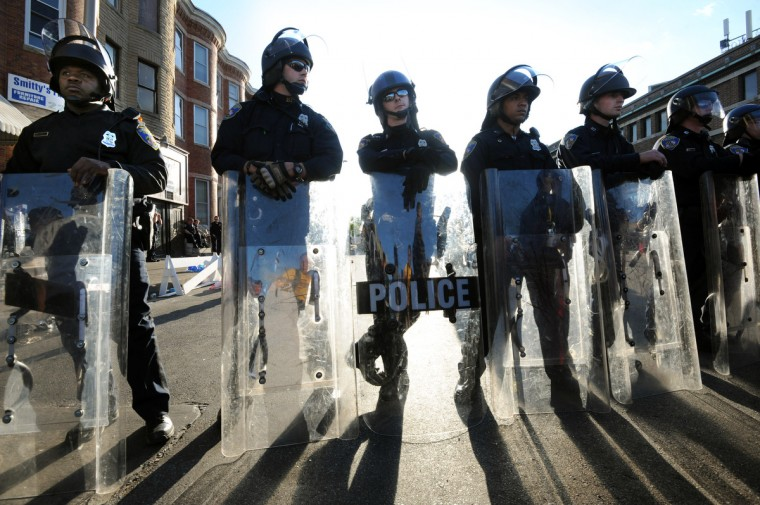Police officers stand at North Ave. and Pennsylvania Ave. twenty-four hours after the rioters destroyed several businesses in the area.  (Algerina Perna/Baltimore Sun)