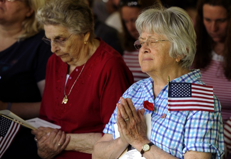 Ginger Parsons of Baltimore, right, prays at the annual Memorial Day Observance at Dulaney Valley Gardens. She is the daughter of World War II veteran Harold Parsons who served in the Army Air Corps during World War II.  (Barbara Haddock Taylor/Baltimore Sun)