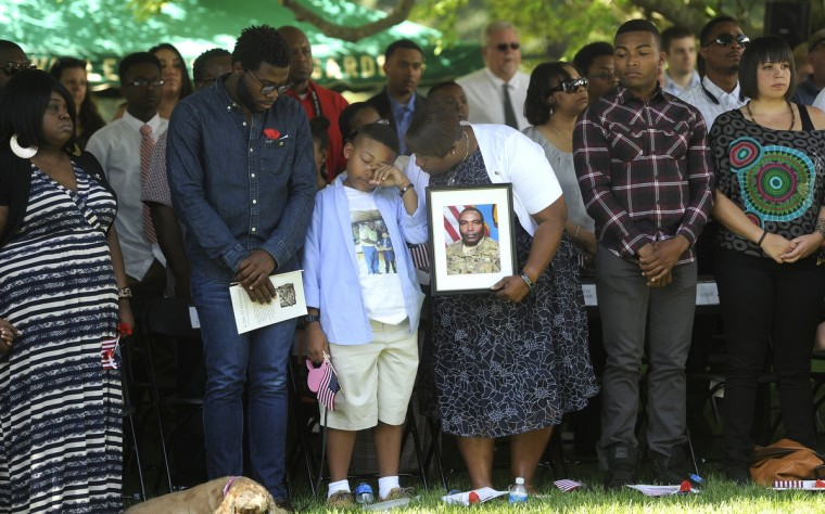 Family members of Sergeant Major Wardell B. Turner, who was honored today, listen  this morning at the annual Memorial Day Observance at Dulaney Valley Gardens. His widow, Katherine Turner, center, holds a photo of him.  His son Xavier, 10, left, wipes a tear. Another son, Specialist Devin A. Turner, 21 is to the right. ( Barbara Haddock Taylor/Baltimore Sun)