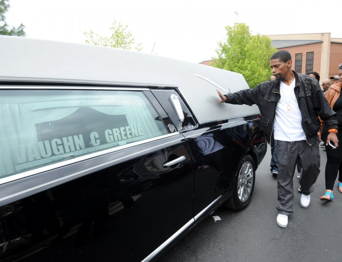 An unidentified man touches the hearse carrying the body of  Freddie Gray after Gray's funeral which was held at New Shiloh Baptist Church. Gray died while in police custody.  (Algerina Perna/Baltimore Sun)