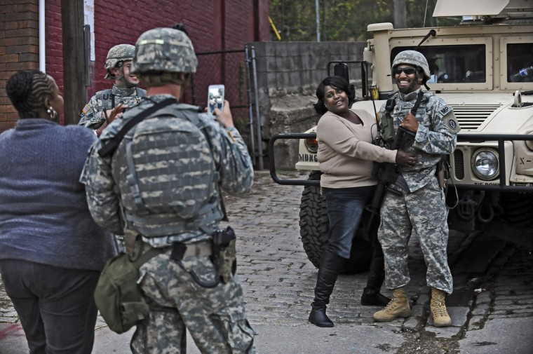 Salyn Kelly, center, a resident on North Avenue near Pennsylvania AVenue, poses for pictures with Staff Sgt. Hopkins, of the Maryland National Guard, as hundreds of people gathered at North and Pennsylvania Avenues to celebrate the news that six Baltimore City police officers have been charged for the death of Freddie Gray while in police custody. (Kenneth K. Lam/Baltimore Sun)