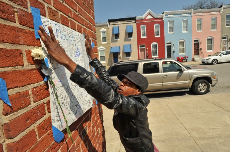 Marshelle Lowery, 47, a resident of Gilmor Homes, tries to put the sign with handwritten messages for Freddie Gray back on the brick wall after it had fallen down. It was posted on the corner of Bakbury Court and Presbury Street at Gilmor Homes, near the location where Freddie Gray was arrested. (Amy Davis/ Baltimore Sun)
