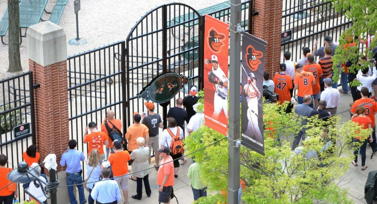 Fans watch from outside Oriole Park at Camden Yards as the Orioles play the Chicago White Sox to an empty stadium because of recent unrest in the city. (Kim Hairston/Baltimore Sun)