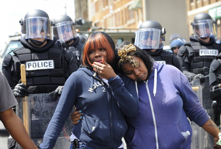 Jerrie McKenny, left, can't hold back the tears as she gets a hug from her sister Tia Sexton during a peaceful protest at North Ave. and Pennsylvania Ave. (Lloyd Fox/Baltimore Sun)