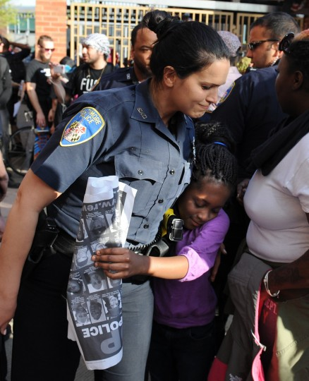Miyana Stokely, 7, of Columbia insisted on hugging Baltimore police officer Eva Tomin before getting on the Metro at Penn North. Miyana and her mother had attended the rally and march from city hall. (Jerry Jackson/Baltimore Sun)