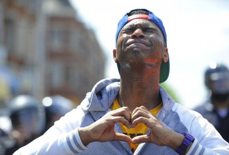 Devante Hill of Baltimore makes a heart with his hands after he was hit with pepper spray after someone threw a bottle at police.  (Lloyd Fox/Baltimore Sun)