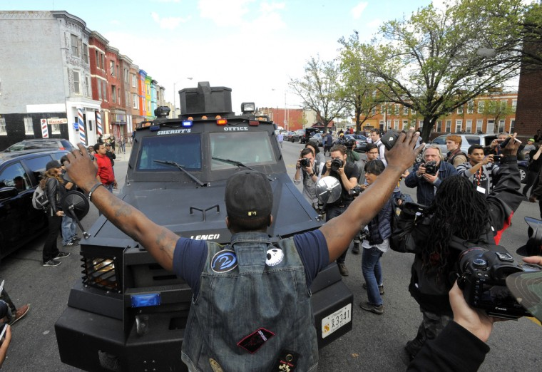 Protesters follow a police vehicle out of the protest area of North Ave.  Tuesday.  (Lloyd Fox/Baltimore Sun)