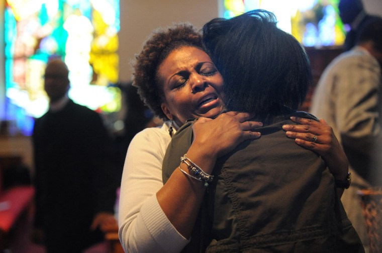Choir member Terry Pulliam, left, embraces Kareema Mills during the morning church services at Fulton Baptist Church at 1630 W. North Ave. on the Sunday following the city uprising last Monday. (Algerina Perna/Baltimore Sun)