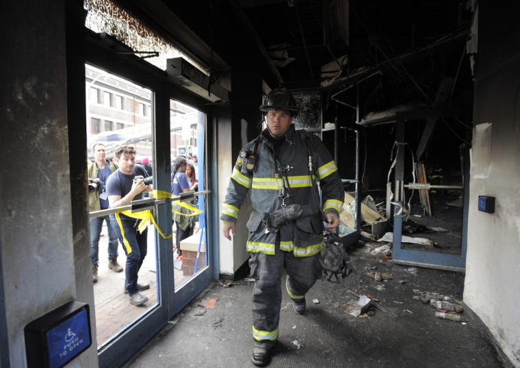 A Baltimore firefighter inspects the burned out the CVS on North Ave. to check out a possible fire in the CVS that burned during rioting yesterday. (Lloyd Fox/Baltimore Sun)