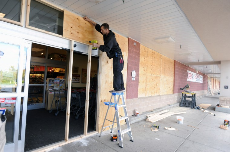 A worker boards up the Weis grocery store near the Security Square Mall in anticipation of more unrest. (Kim Hairston/Baltimore Sun)