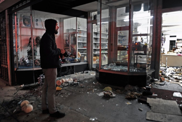 A man stopped to take pictures of a wig store, at 2100 block of West Pratt Street,  that has been ransacked by looters as Baltimore City. (Kenneth K. Lam/Baltimore Sun)