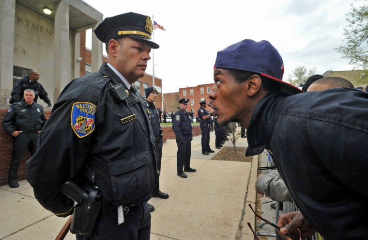 An unidentified man at right challenges Baltimore City police officer C. A. Thompson, as they stood in a line behind a barricade in front of the Western District police station Thursday evening. (Amy Davis/ Baltimore Sun)