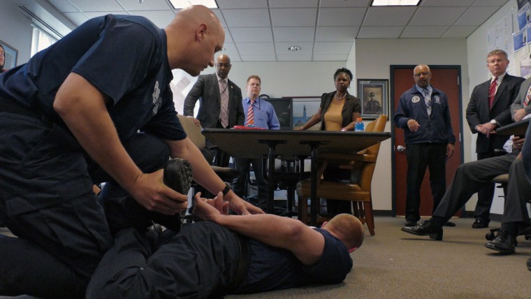 "Addressing the group of investigators, Dr. David L. Higgins, MD, P.C. gives his opinion about injuries or blood flow to the lower extremities at the position demonstrated by police training instructors (left) while Baltimore Police Major Stanley Brandford (standing next to Higgins) as the instructors attempt to mimic the position known as a ""leg lace"" in which Freddie Gray was when he was placed under arrest after watching a cellphone video of the arrest. (Karl Merton Ferron/Baltimore Sun)"