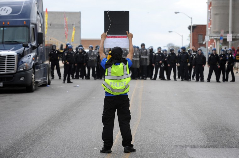 A protester with a stolen police vest taunts Baltimore Police on Pennsylvania Ave during Monday's riot. (Jerry Jackson/Baltimore Sun)