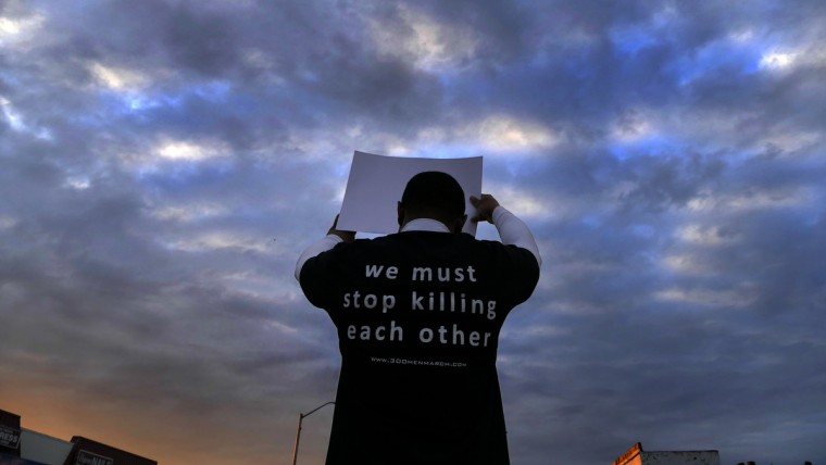 A protester holds a sign as the 300 Man March stands at the intersection of Cold Spring Lane and Park Heights Avenue at sunset. The city state's attorney today announced charges against six officers who confronted and then placed Gray into custody on April 12, eventually resulting in what was ruled a homicide of the 25-year-old West Baltimore resident seven days later. (Karl Merton Ferron/Baltimore Sun)