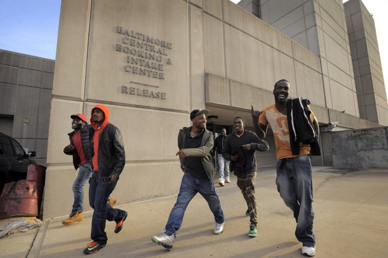 A number of men react to the smell and sight of freedom, released from central booking as the sun sets. Over 100 people were released of the of the more than 200 arrested during the recent protests. (Karl Merton Ferron/Baltimore Sun)