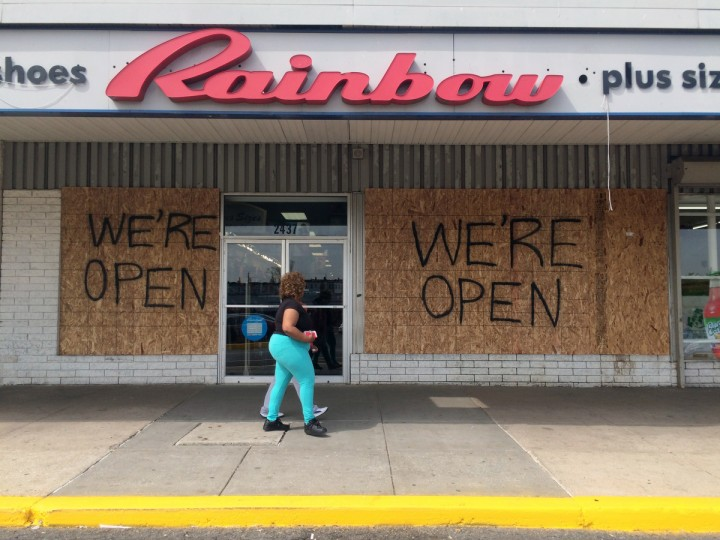 A clothing store remains boarded but open at the Westside Shopping Center after being targeted during Monday's rioting. (Karl Merton Ferron/Baltimore Sun)