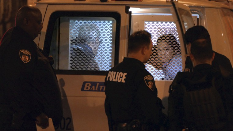 Several protesters sit in a police transfer van when police aggressively pushed defiant and peaceful protesters off the City Hall lawn at the start of the daily curfew. (Karl Merton Ferron/Baltimore Sun)