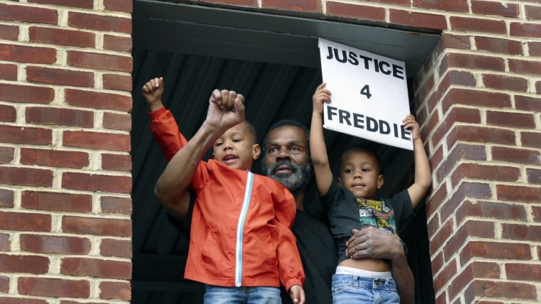 Michael Pulley with his two 4-year-old grandsons watch from a second floor balcony in support of the family as residents return from a march to the Western District of the Baltimore Police following the death of local resident Freddie Gray. (Karl Merton Ferron/Baltimore Sun)