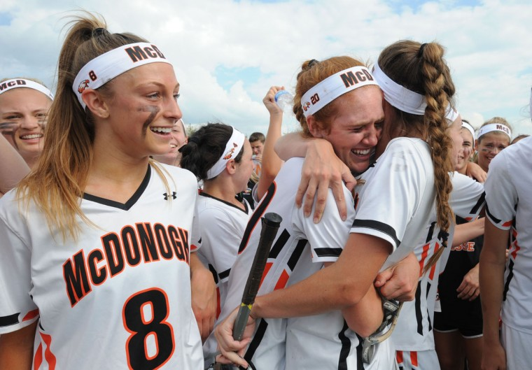 In the foreground are McDonogh players from left, Sophie Alecce #8, and Elizabeth George #20 hugging Savannah Buchanan #9. McDonogh celebrates after winning the IAAM lacrosse championship on 5/10/15 aganst Roland Park Country School with a score of 15-14. (Algerina Perna/BSMG)
