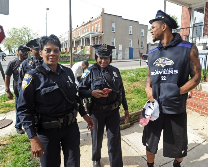 Ravens' Jimmy Smith, right, borrows a police hat from Baltimore police officer Monica Cooper, left, as they and officer Chantell English, center, walk to Matthew Henson Elementary School. Baltimore Ravens players, coaches and staff visited Matthew Henson Elementary School and Frederick Douglass High School to provide positive support in light of the recent riots and looting in the city. The Ravens helped unload donated food at the elementary school. (Kenneth K. Lam/Baltimore Sun)