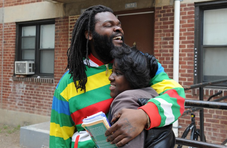 Kevin Moore hugs Kiona Mack in a courtyard at Gilmor Homes after news of charges brought against  six Baltimore police officers in the death of Freddie Gray. Both captured cellphone video of Gray's arrest that has been key in getting national attention for the case. (Jerry Jackson/Baltimore Sun)