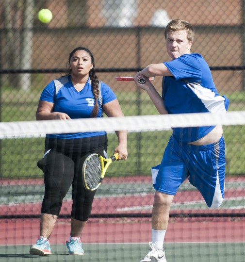 Annapolis'  Nate Vance, with teammate Jennifer Reyez, smashes the ball in a match with South River's Tyger Hanback and Grace MacMillan at South River High School in Edgewater. (Joshua McKerrow/BSMG)
