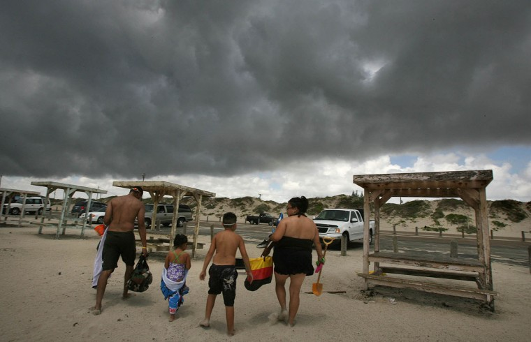 The Rocha family, Chris, Marissa, 3, Christian, 9, and Letty, from left, retreat to their vehicle at Padre Balli Park in Corpus Christi, Texas as a rain band pushes in from the Gulf of Mexico on Tuesday, July 22, 2008. Forecasters say Dolly was expected to dump 15 to 20 inches of rain and bring coastal storm surge flooding of 4 to 6 feet above normal high tide levels. (AP Photo/Corpus Christi Caller-Times,Todd Yates)
