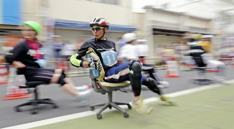 """Participants in the Isu-1 Grand Prix's endurance race push through the Tokiwacho shopping street, with its many closed stores, on office chairs in Kurashiki, Okayama Prefecture, on May 9. There is no rule regarding how one sits on the chair. The event's slogan is, """"""""Will the chair break down first, or will you?"""""""" (Yomiuri Shimbun)."""