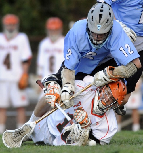 C. Milton Wright's Michael Logan, top, and Fallston's Tommy Bracken battle for a ground ball in the first half of a high school lacrosse game in Fallston Friday, April 17, 2015. (Steve Ruark for BSMG)