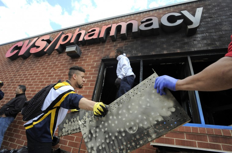 Volunteers work to help clear out the debris from the CVS on North Avenue that burned Monday.  (Lloyd Fox/Baltimore Sun)