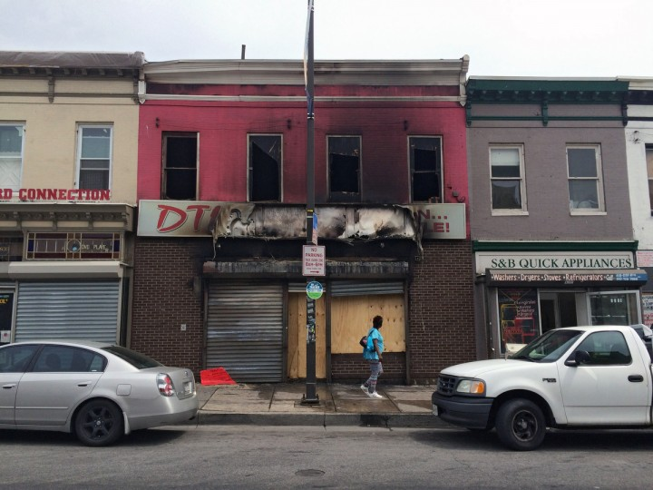 The exterior of the DTLR clothing store on Pennsylvania Avenue is seen after being burned during the initial uprising. (Karl Merton Ferron/Baltimore Sun)