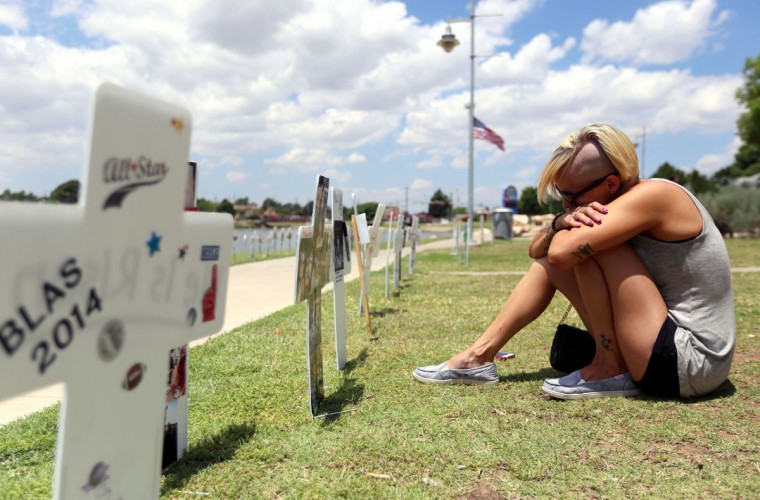 Heather Welch sits in front two crosses placed in memory of her sister Heidi Evans at the Compassionate Friends of West Texas memorial walk and butterfly release Saturday May 16, 2015 at Memorial Gardens Park in Odessa, Texas. (Edyta Blaszczyk/Odessa American via AP)