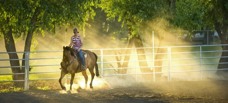In this late evening Thursday, May 28, 2015 photo, Jordan Berquist rides through the dust in an arena just outside Walla Walla, Wash. Berquist was getting some exercise for her horse. (Greg Lehman/Walla Walla Union-Bulletin via AP)