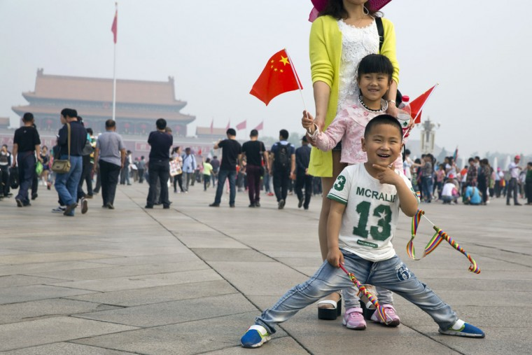 Visitors to Tiananmen Square pose for photos in Beijing, Friday, May 1, 2015. Millions of Chinese are taking advantage of the May Day holidays to visit popular tourist sites. (AP Photo/Ng Han Guan)