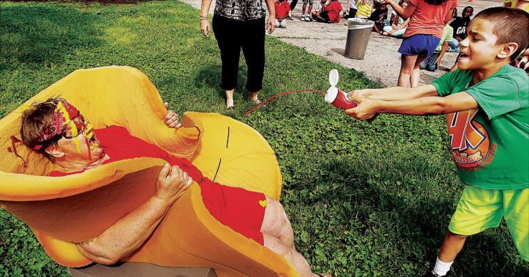 "A student, right, squirts ketchup on Eunice Smith School social skills tutor Sherry Droste as she sits in a chair while wearing a foam rubber ""bun"" to be a human hot dog Wednesday May 27, 2015, in Alton, Ill. The school allowed students to each dump one condiment of ketchup, mustard, relish, chili or cheese on Droste as a reward for receiving one or fewer disciplinary referrals in the last month of school. (John Badman/The Telegraph via AP)"