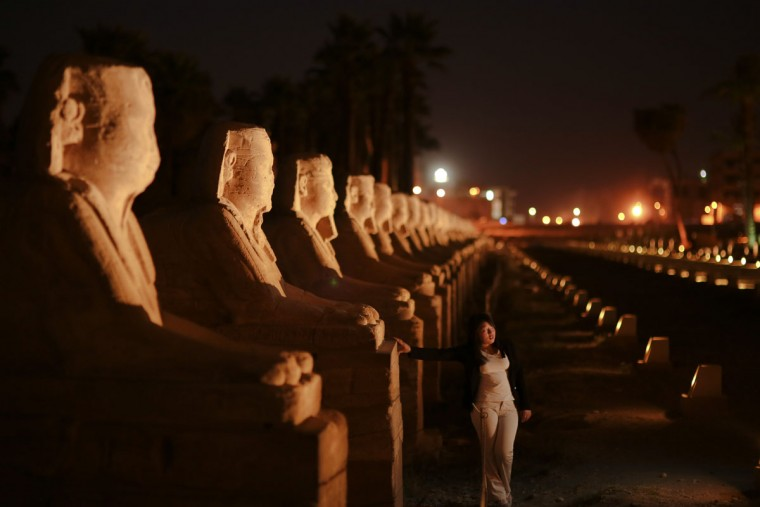 In this Friday, May 1, 2015 photo, a tourist poses for a photo in front of the avenue of sphinxes at Luxor Temple, in Luxor, 510 kilometers (320 miles) south of Cairo, Egypt. (AP Photo/Mosa'ab Elshamy)