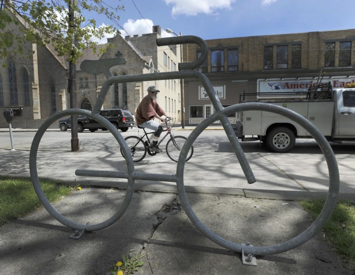 A bicyclist pedals past bicycle-shaped rack in central park Friday, May 1, 2015, in Johnstown, Pa. (Todd Berkey/The Tribune-Democrat via AP)