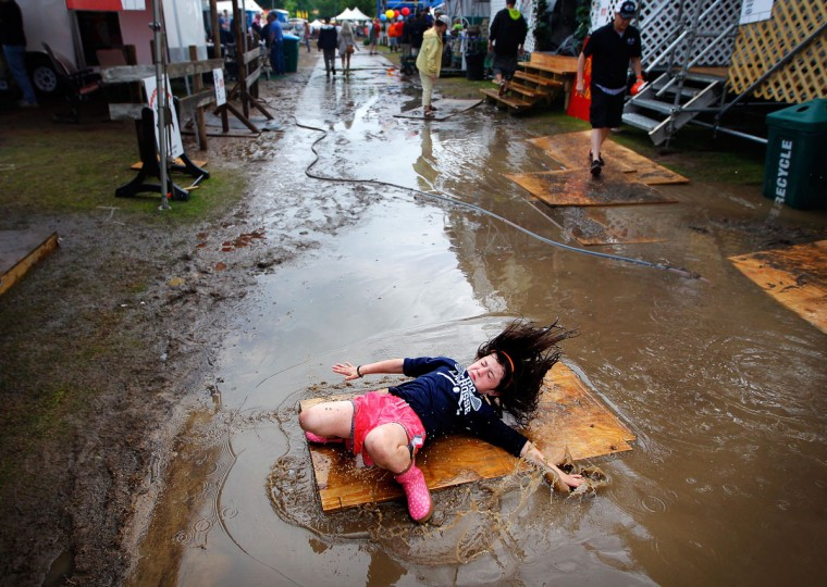 Charlotte Stakem, 8, takes a spill while turning cartwheels on a chunk of plywood at the Memphis In May World Championship Barbecue Cooking Contest at Tom Lee Park Saturday, May 16, 2015 in Memphis. (Jim Weber/The Commercial Appeal via AP)