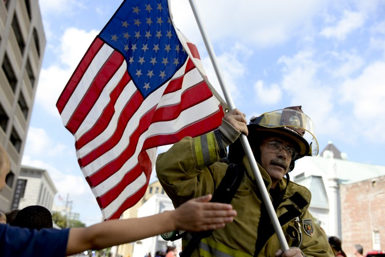 Bryan County fire fighter John Andriotis runs passed fans attempting to give high fives while carrying the American Flag during the Savannah Mile in Savannah, Ga. Soldiers, military serviceman, police officers, and fire fighters ran the mile in full uniform. (Ian Maule/Savannah Morning News via AP)