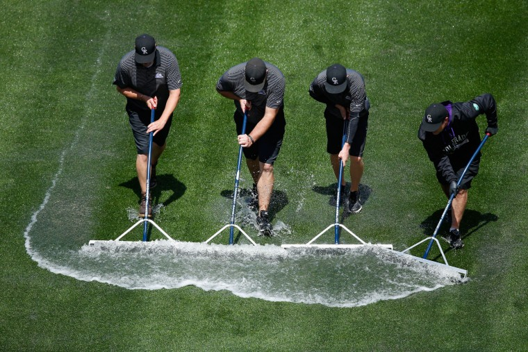 The grounds crew squeegee water out of left field after removing the tarp as rain delayed the start of the game between the San Francisco Giants and the Colorado Rockies during the first game of a double header at Coors Field in Denver. (Doug Pensinger/Getty Images)