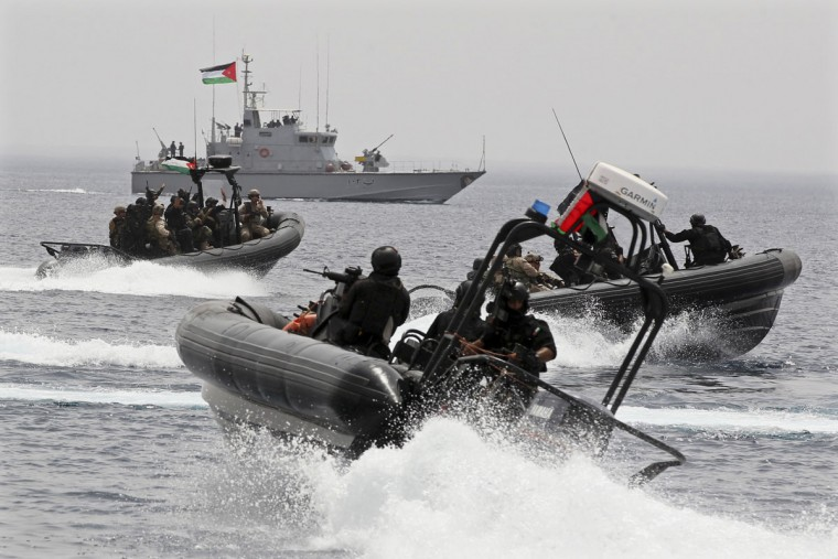 "Jordanian forces practice a drill to free a ship seized by mock terrorists during 18-nation military exercises off Aqaba's seaport, 330 kilometers (205 miles) south of Amman, Jordan, Monday, May 18, 2015. Some 10,000 troops took part in the two-week ""Eager Lion"" exercises hosted by Jordan for the fifth year. (AP Photo/Raad Adayleh)"