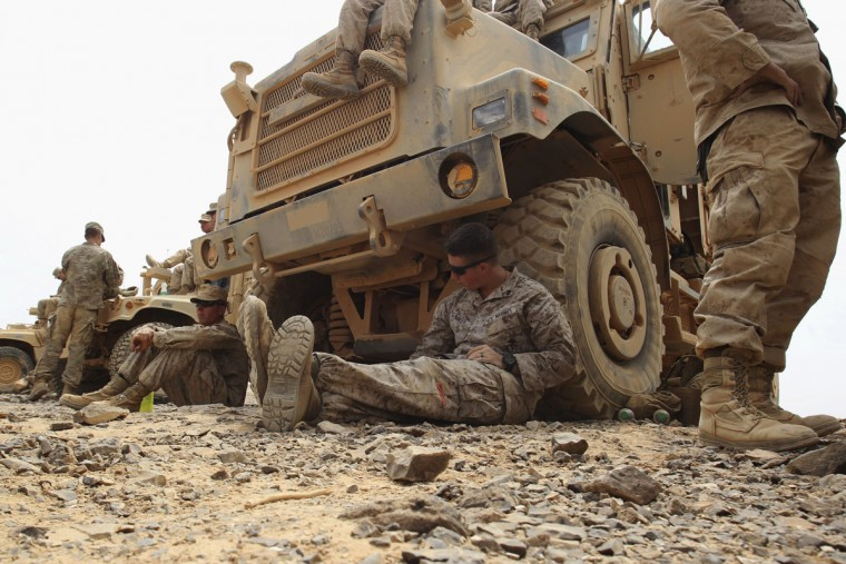 "U.S. soldiers take a break during 18-nation military exercises in a field near the border with Saudi Arabia, in Mudawara, 280 kilometers (174 miles) south of Amman, Jordan, Monday, May 18, 2015. Some 10,000 troops took part in the two-week ""Eager Lion"" exercises hosted by Jordan for the fifth year. (AP Photo/Raad Adayleh)"